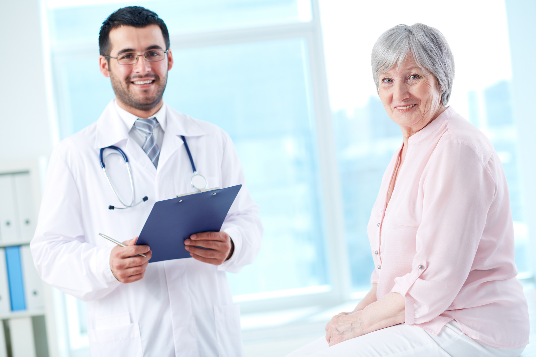 Confident doctor with stethoscope and clipboard and his senior patient looking at camera