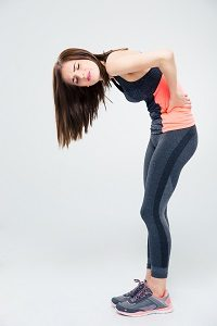 Full length portrait of a sporty woman having back pain over gray background