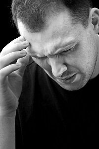 A man with an intense headache or migraine in black and white. He might be experiencing stress during a time of economic crisis or other hardship.