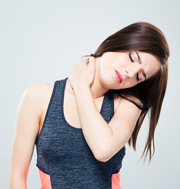 Fitness young woman with neck pain over gray background