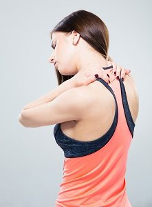 Sporty woman having back pain over gray background